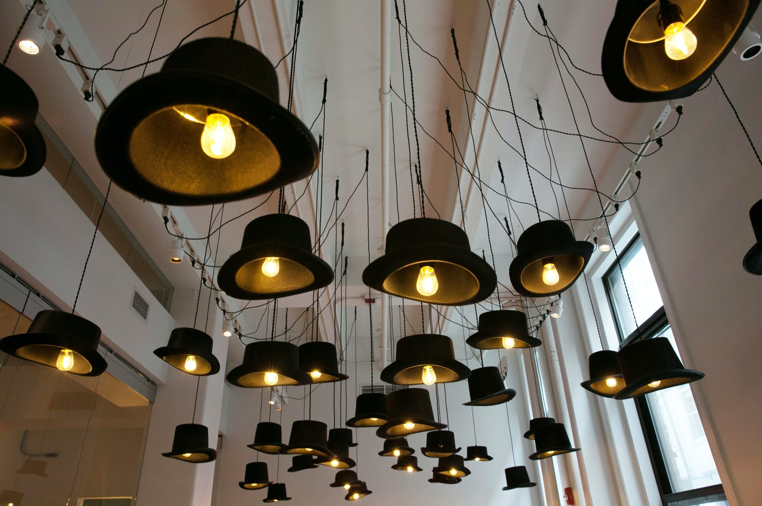 Light bulbs in top hats hanging from the ceiling